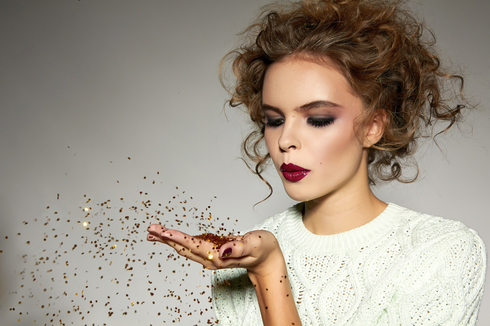 woman blowing glitter